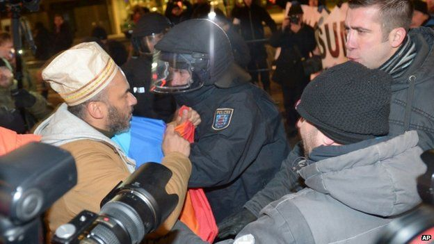 A police officer separates an anti-Pegida protester (left) and Pegida supporters in Leipzig