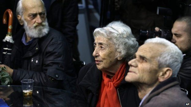 Elderly supporters of Conservative Prime Minister Antonis Samaras watch the exit poll results at the election kiosk of New Democracy party in Athens, Sunday, Jan. 25, 2015