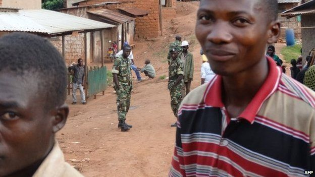 Burundian army men patrol in Rwesero as villagers carry on their daily life on 6 January 2015
