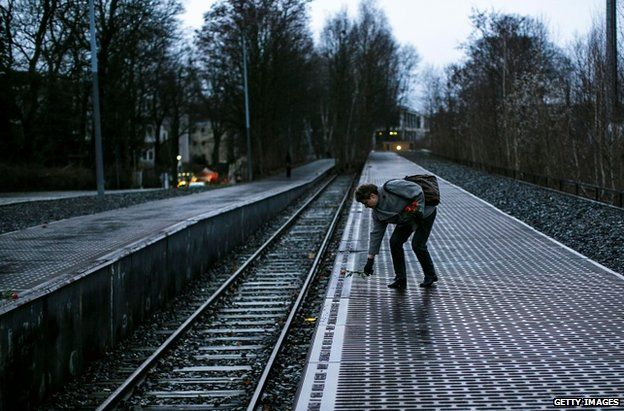 A woman leaves a rose next to one of the many plaques detailing transports of Berlin Jews to concentration camps at Track 17 in Berlin, 27 January