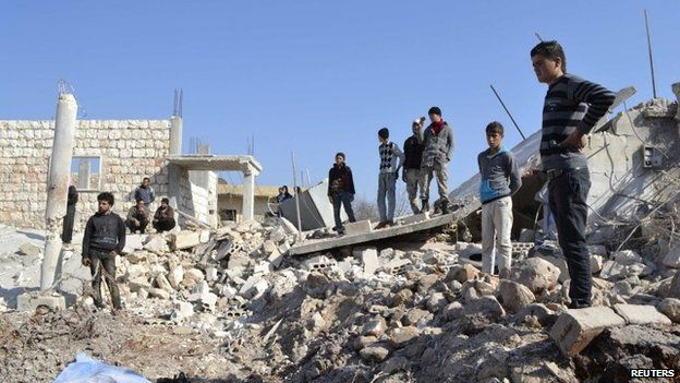 """Residents inspect a site damaged by what activists said were barrel bombs thrown by warplanes loyal to Syria""""s President Bashar Al-Assad in Kansaghra village, Jabal al-Zawiya in the southern countryside of Idlib 25 January 2015."""