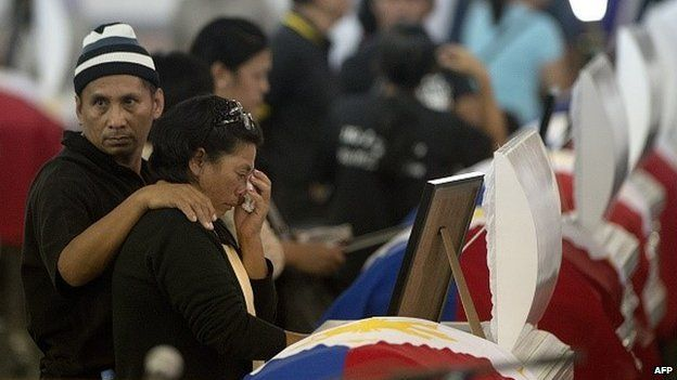 Relatives cry at the coffin of one of the 44 police commandos killed in a botched anti-terror operation during a service at the Camp Bagong Diwa, in Manila on January 30, 2015.