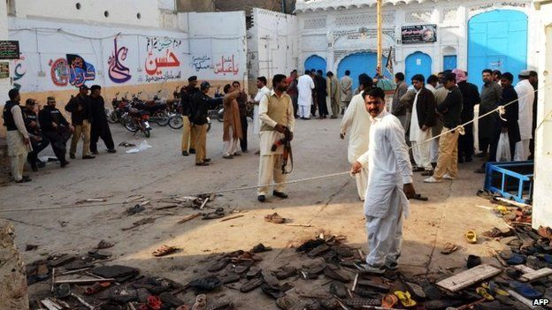 Pakistani security officials gather at the scene following a bomb attack at a Shiite Muslim mosque in Shikarpur in Sindh province