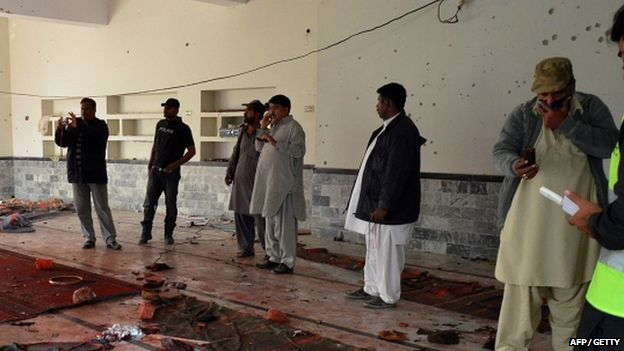 Pakistani security officials gather at a mosque after a bomb explosion in Shikarpur in Sindh province,