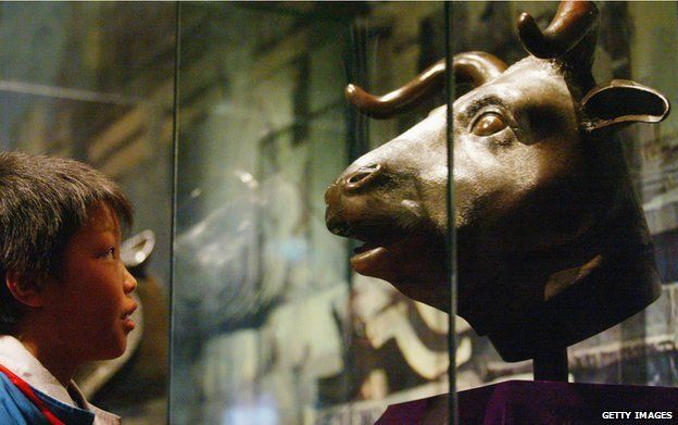 A boy views the ox bronze head of Qing Dynasty (1644-1911) at a special exhibition April 28, 2005 in Shenyang of Liaoning Province, China. Four pieces of famous bronze heads including a tiger, a pig, an ox and a monkey of Qing Dynasty art treasure make their debut in Shenyang during the exhibition. They are among the 12 Chinese zodiac sculptures which originally placed in the Old Summer Palace in Beijing. The bronze set were taken out of the country in 1860 by British and French archaeologists. In 2000, the Beijing-based Poly Group bought the heads of the ox, tiger and monkey for more than RMB 30 million (USD 3.66 million) at an auction and returned them to the Chinese mainland. The pig head returned to China after it was purchased from the United States by Macao magnate Stanley Ho for RMB 6 million (USD 720,000) in 2003.