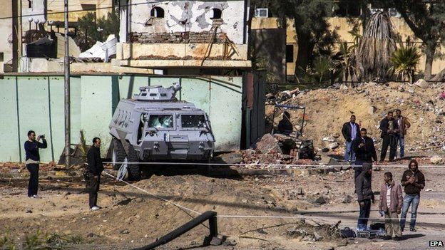 Egyptian security officers and local residents inspect the damage caused by the attack in El-Arish, 30 January 2015