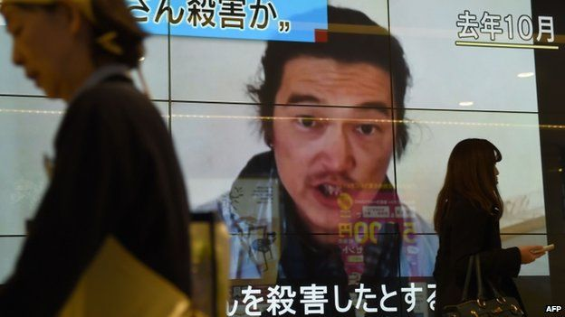 People walk past a big screen reporting that a Japanese hostage was killed by the Islamic State