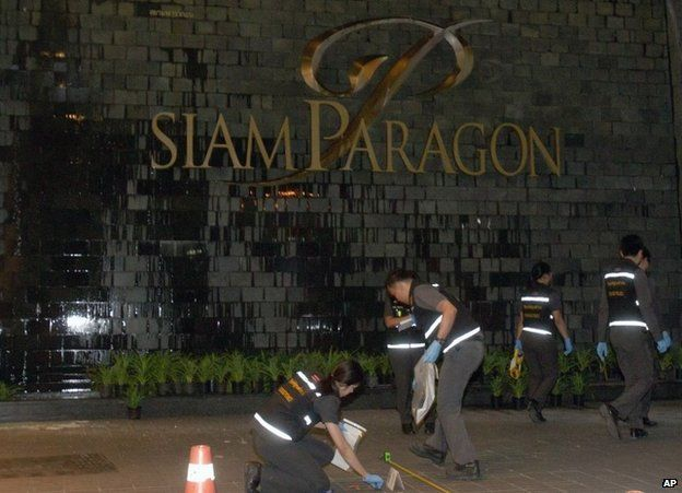 Thai police forensic officers investigate near the front of the Siam Paragon shopping mall, the site of a blast in Bangkok, Thailand, Sunday, Feb. 1, 2015.