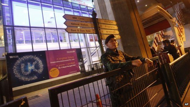 A Thai soldier stands guard as forensic police officers investigate near the front of Siam Paragon shopping mall, the site of a blast in Bangkok, Thailand, Sunday, Feb. 1, 2015.