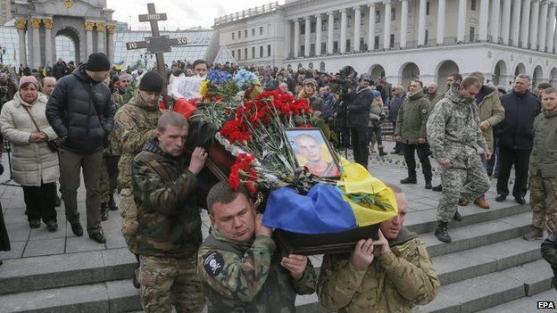 Aidar battalion volunteers carry a coffin with body of their friend, who was killed in eastern Ukraine conflict, during the funeral ceremony on the Independence Square in Kiev, Ukraine, 2 February 2015