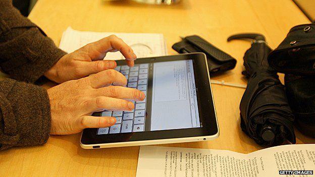 Man writes email on an iPad