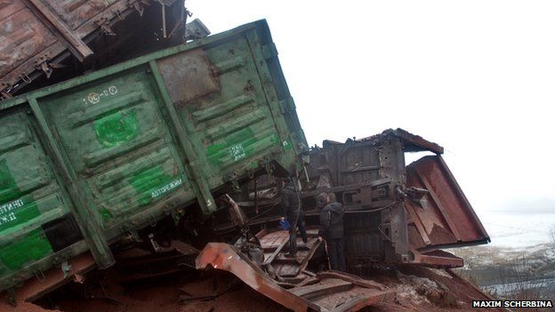 Railway workers inspecting derailed carriages