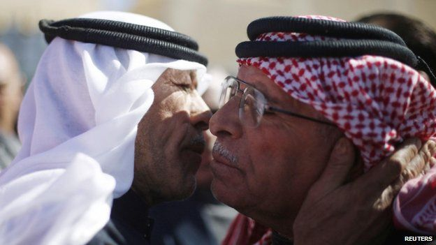Saif al-Kasasbeh (right), father of Jordanian pilot Muath al-Kasasbeh, greets a mourner who turned up at the headquarters of the family's clan in the city of Karak (04 February 2015)
