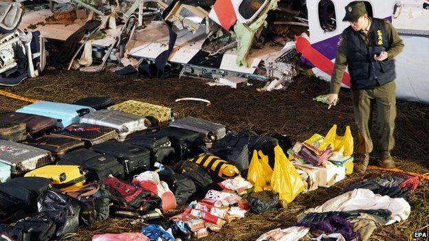 A military police officer inspects passengers' luggage recovered from the wreckage of the TransAsia Airways plane early on 5 February 2015