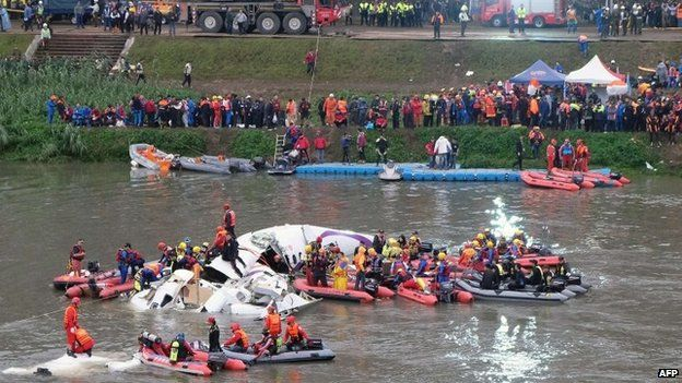 Rescue personnel search for passengers from the wreckage of a TransAsia plane that crash-landed in the Keelung river in Taipei on 4 February 2015