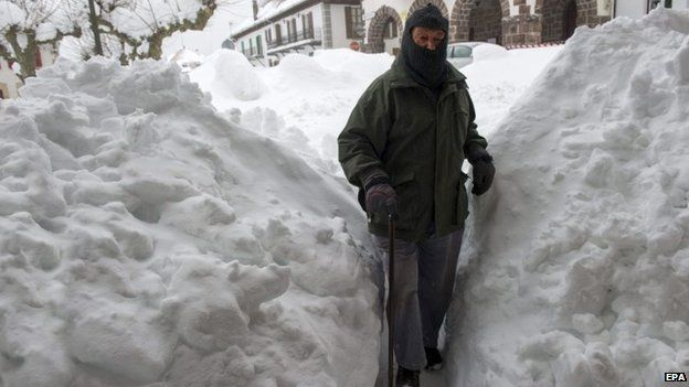 An elderly man makes his way through a path flanked by high piles of snow in Burguete town, Navarre region, northern Spain, 4 February 2015