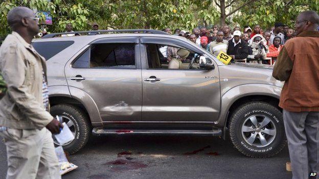 Onlookers gather at the scene after a Kenyan lawmaker was shot dead by gunmen on a main street in Nairobi, Kenya