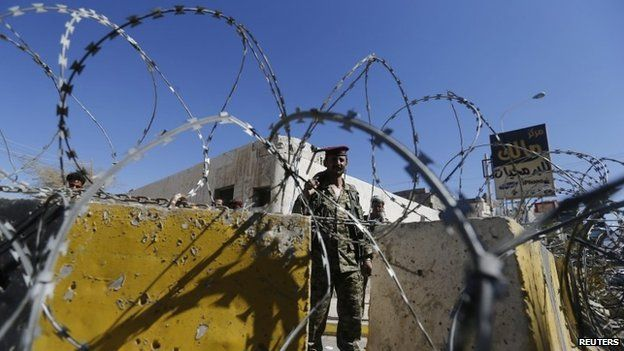 A soldier stands guard behind a roadblock in the Yemeni capital Sanaa