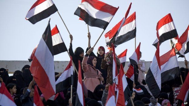 Supporters of Houthi Shiites, who took over the government of Yemen and installed a new committee to govern, wave national flags at a rally