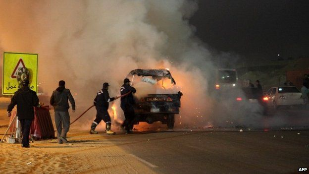 Egyptian firefighters extinguish fire from a vehicle outside a sports stadium in a Cairo's northeast district