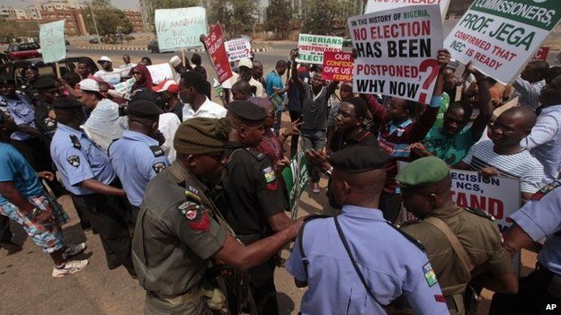 Protestors hold banners during a protest in Abuja, Nigeria, Saturday, Feb. 7, 2015