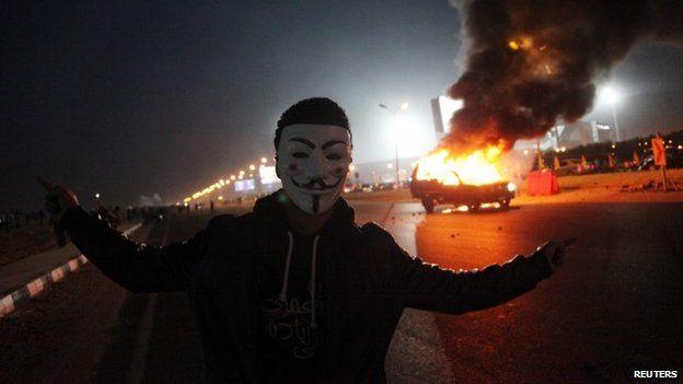 "An Egyptian Zamalek soccer club fan wearing a Guy Fawkes mask near a burning police car outside a sports stadium in Cairo""s northeast district"