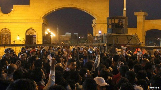 Policemen and soccer fans argue as fans attempt to enter a stadium to watch a match, on the outskirts of Cairo