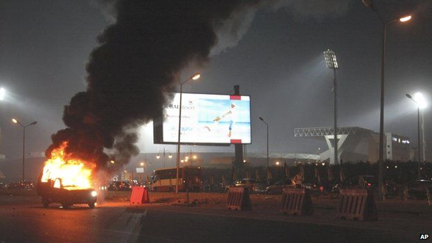 A pickup truck bursts into flames as a riot breaks out outside of a soccer match between Egyptian Premier League clubs Zamalek and ENPPI at Air Defense Stadium in a suburb east of Cairo