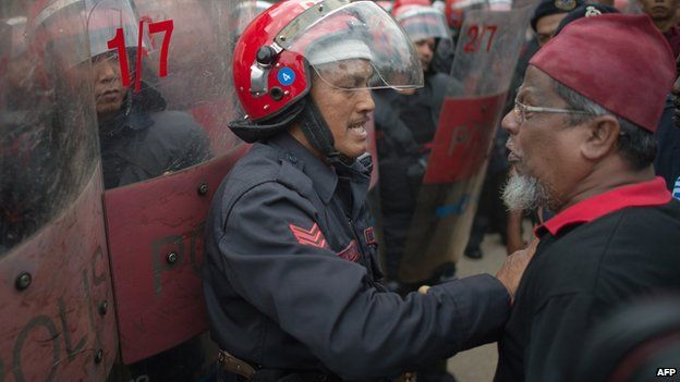 A Malaysian riot policeman (L) tries to control a supporter (R) of Malaysian opposition leader Anwar Ibrahim after Anwar's appeal on a sodomy conviction was rejected outside the federal court in Putrajaya, outside Kuala Lumpur on February 10, 2015.