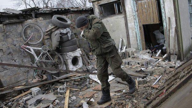 A man examines debris at a destroyed garage after shelling in Donetsk, Ukraine - 11 February 2015