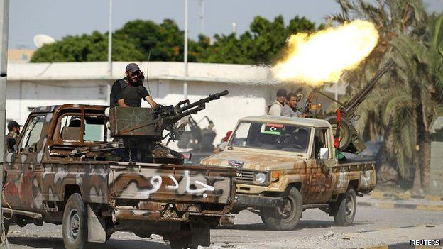 Libyan rebel fighter fires from vehicle towards Bab al Aziziya compound in Tripoli. 23 August 2011.
