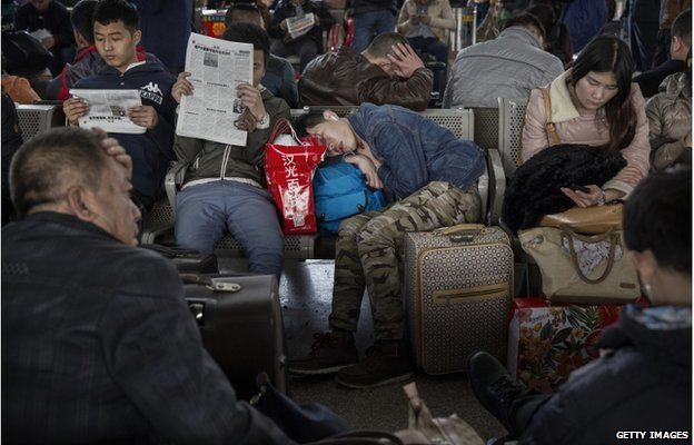 A Chinese traveller sleeps as others read and relax as they wait to leave for the Spring Festival at a local railway station on 17 February 2015 in Beijing, China.
