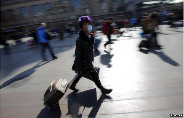 A man walks with his suitcase as he heads to a platform at a railway station in Beijing 17 February 2015.