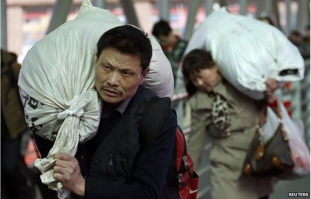 Passengers carry their belongings in sacks as they head to a platform at a railway station in Beijing 17 February 2015.