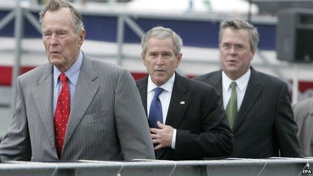 """A file picture dated 07 October 2006 shows then US president George W. Bush (C) walking with his father the former President George H.W. Bush (L), and his brother then Florida Governor Jeb Bush following a christening ceremony the US Navy""""s new aircraft carrier the George H.W. Bush, at the Northrop Grumman shipyard in Newport News, Virginia."""