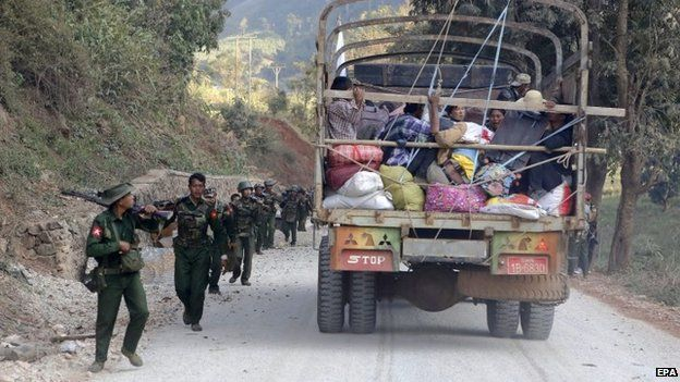 A rescue truck loaded with fleeing locals passes armed military troops near self-administered Kokang capital Laukkai, northern Shan State, Myanmar, 17 February 2015