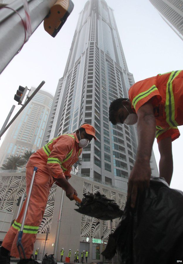 Workers clean up debris from the Torch skyscraper in Dubai