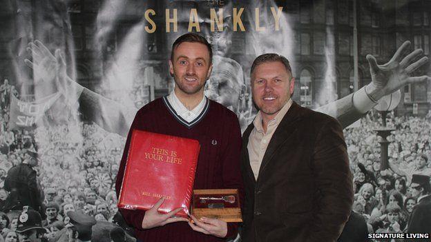 Bill Shankly's grandson Chris Carline holding memorabilia
