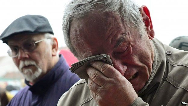 A man reacts emotional as residents pay respect to the victims of a shooting at a restaurant in the city of Uhersky Brod, Czech Republic, 25 February 2015.