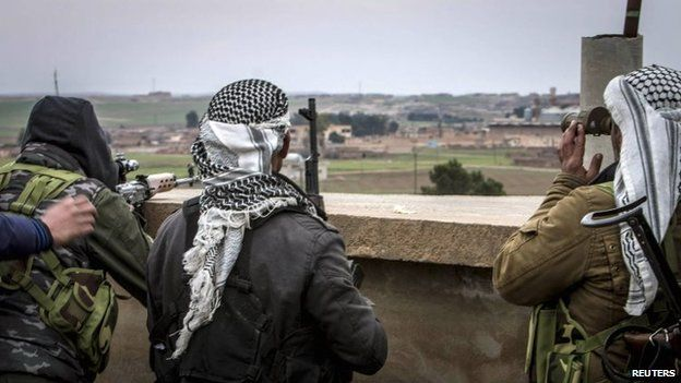 Fighters of the Kurdish People's Protection Units (YPG) carry their weapons and use a pair of binoculars in the outskirts of Tal Tamr town as they monitor the movements of Islamic State fighters