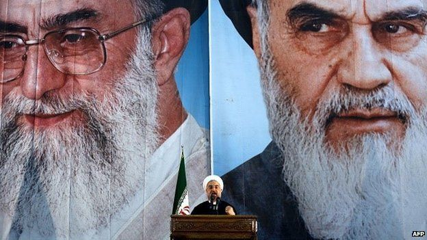 Iranian President Hassan Rouhani delivers a speech under portraits of Iran's supreme leader, Ayatollah Ali Khamenei (L) and Iran's founder of the Islamic Republic, Ayatollah Ruhollah Khomeini (R), on the eve of the 25th anniversary of the Islamic revolutionary leader Ayatollah Ruhollah Khomeini's death, at his mausoleum in a suburb of Tehran on 3 June 2014