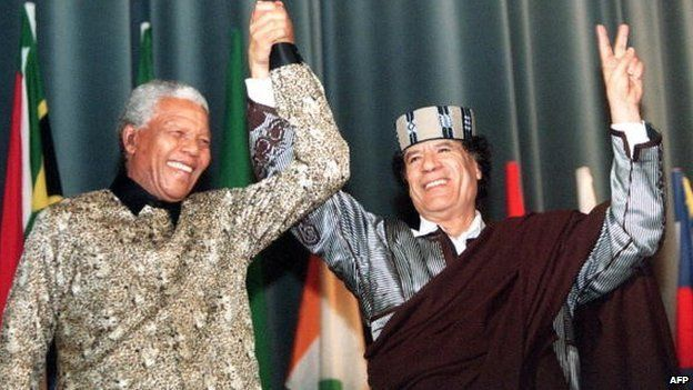 Libyan Leader Muammar Gaddafi flashes the 'V' sign as he stands with South African President Nelson Mandela on 19 March 1999 at the end of their speeches at the Libyan parliament in Tripoli