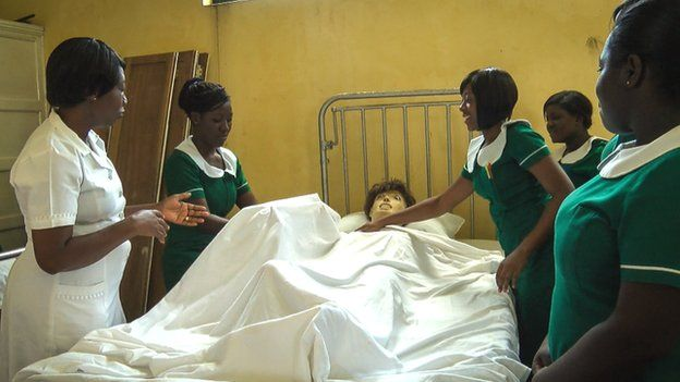 Trainee nurses in Ghana with a dummy patient in bed