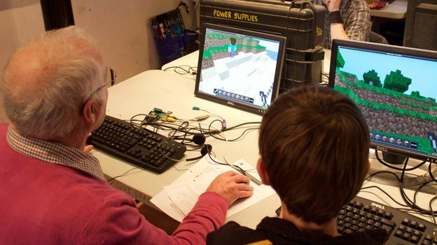 Older man and child at coding event