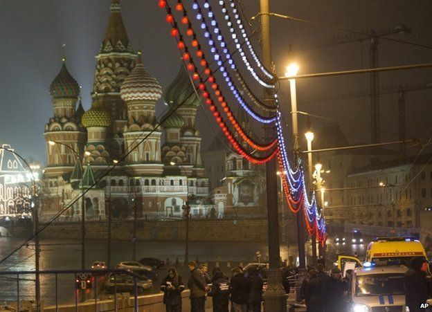 Police stand around the body of Boris Nemtsov in Moscow, with St Basil's Cathedral and the Kremlin in the background, 27 February