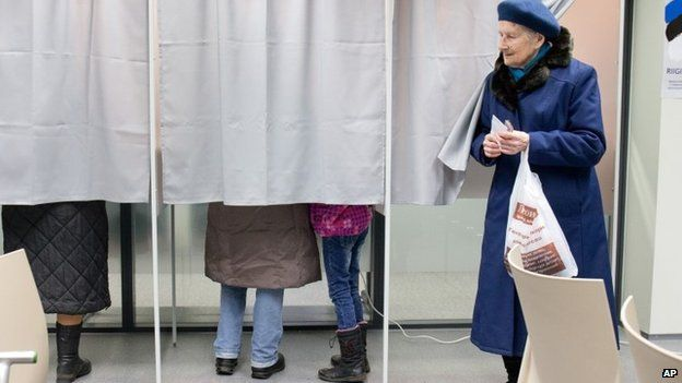A woman leaves a voting booth at a polling station in Tallinn, Estonia, on Sunday, March 1, 2015