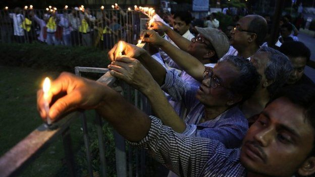 Indian people put candles onto a fence as they protest against the killing of Avijit Roy, a prominent Bangladeshi-American blogger, in Kolkata, India, Sunday, March 1, 2015