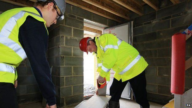 David Cameron tries his hand at carpentry with apprentice Kial Foye during a visit to the Barratt Homes Evolve development in Grays, Essex