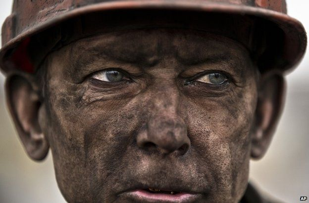 A miner rests after helping in the search for bodies at Zasyadko Mine, eastern Ukraine, 4 March