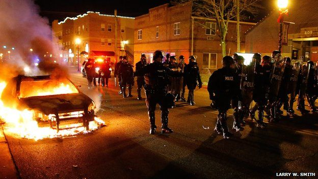 Row of police in riot gear beside a burning car